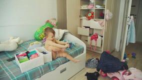 Bebé lindo que intenta en la ropa en dormitorio sucio almacen de video