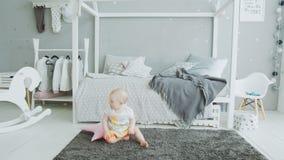 Bebé lindo que intenta levantarse de piso en casa metrajes