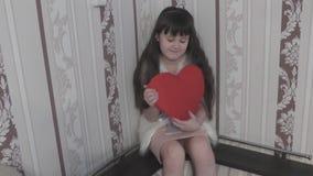 Bebé lindo que juega con el corazón del peluche almacen de metraje de vídeo