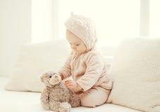 Bebé lindo que juega con el hogar del juguete del oso de peluche en el sitio blanco Fotos de archivo libres de regalías