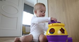 Bebé lindo que juega con el juguete colorido que se sienta en piso almacen de metraje de vídeo