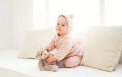 Bebé lindo que juega con el juguete del oso de peluche en casa en el sitio blanco Imagen de archivo libre de regalías
