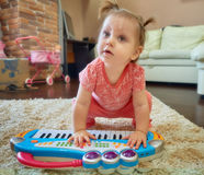 Bebé lindo que juega con el piano del juguete Fotos de archivo libres de regalías