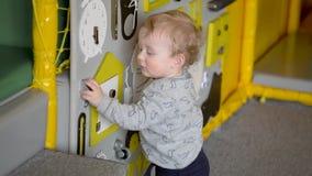 Bebé lindo que juega con el tablero ocupado en la pared Juguetes educativos Ocupado-tablero para los niños metrajes