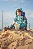 Bebé lindo que juega con la arena en una salvadera imagenes de archivo