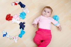 Bebé lindo que juega con las vendas coloridas Imagenes de archivo