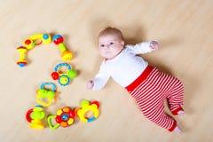 Bebé lindo que juega con los juguetes coloridos del traqueteo Imagen de archivo