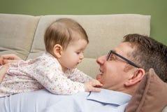 Bebé lindo que juega con su padre feliz en un sofá Foto de archivo