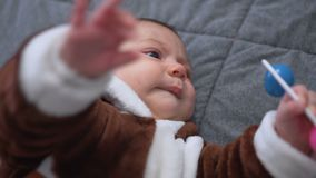 Bebé lindo que juega el juguete Niño lindo que juega con traqueteo en cama almacen de video