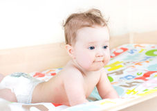 Bebé lindo que juega en una cama que lleva un pañal Fotos de archivo libres de regalías