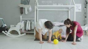Bebé lindo que juega la bola que se arrastra con los padres en casa almacen de metraje de vídeo