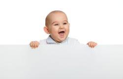 Bebé lindo que lleva a cabo a la tarjeta en blanco vacía Imágenes de archivo libres de regalías