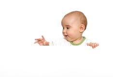 Bebé lindo que lleva a cabo a la tarjeta en blanco vacía Fotografía de archivo