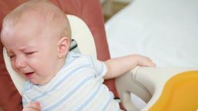 Bebé lindo que llora en la silla en casa almacen de video