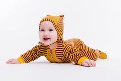 Bebé lindo que miente en abejas de un traje en un fondo blanco Foto de archivo libre de regalías
