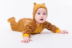 Bebé lindo que miente en abejas de un traje en un fondo blanco Imagenes de archivo