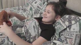 Bebé lindo que miente en la cama, jugando con el oso de peluche almacen de metraje de vídeo
