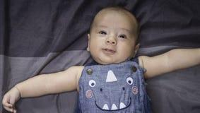 Bebé lindo que miente en una mezclilla que lleva de la gota foto de archivo