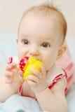 Bebé lindo que miente y que lame el juguete foto de archivo