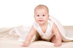 Bebé lindo que mira a escondidas hacia fuera de debajo la manta Fotos de archivo