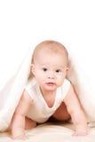 Bebé lindo que mira a escondidas hacia fuera de debajo la manta Fotografía de archivo libre de regalías