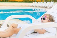 Bebé lindo que se relaja en sunbed cerca de piscina en Hawaii, hotel Fotografía de archivo