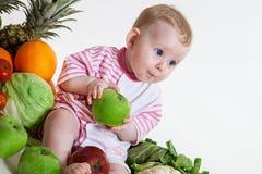 Bebé lindo que se sienta con las frutas y verduras imagen de archivo