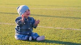 Bebé lindo que se sienta en el campo de fútbol Concepto activo de la niñez metrajes