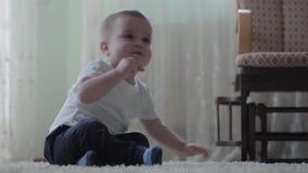 Beb? lindo que se sienta en el piso en la alfombra mullida que juega solamente El muchacho se levanta La mujer viene, coge al ni? almacen de metraje de vídeo