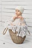 Bebé lindo que se sienta en una cesta Foto de archivo libre de regalías