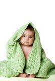Bebé lindo que se sienta entre la manta verde. Imagen de archivo