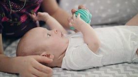 Bebé lindo que sostiene el juguete azul Desarrollo recién nacido del niño Mundo precioso del estudio del niño metrajes