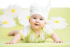 Bebé lindo sonriente que miente en verde Imágenes de archivo libres de regalías