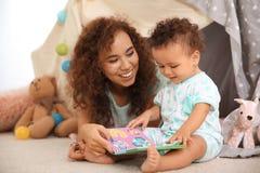 Bebé lindo y madre que juegan en piso imagenes de archivo