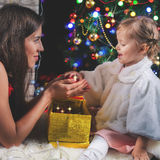 Bebé lindo y momia que adornan un árbol de navidad Bolas rojas Imagen de archivo libre de regalías