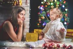 Bebé lindo y momia que adornan un árbol de navidad Bolas rojas Imagen de archivo