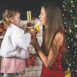 Bebé lindo y momia que adornan un árbol de navidad Bolas rojas Fotografía de archivo