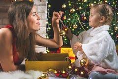 Bebé lindo y momia que adornan un árbol de navidad Bolas rojas Imágenes de archivo libres de regalías