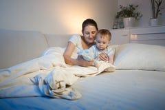 Bebé lindo y su madre que juegan con el juguete en cama antes de ir a Fotografía de archivo libre de regalías