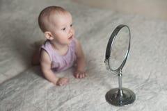 Bebé llying en cama y que mira su reflexión en espejo Fotografía de archivo