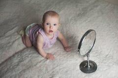 Bebé llying en cama y que mira su reflexión en espejo Imágenes de archivo libres de regalías