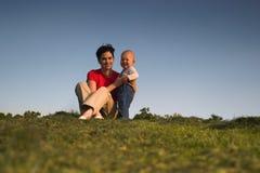 Bebé, madre, hierba y cielo imagen de archivo