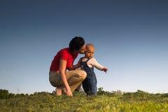 Bebé, madre, hierba y cielo imagenes de archivo