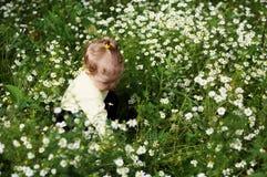 Bebé-muchacha con las flores Fotos de archivo libres de regalías