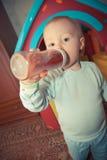 Bebé novo com o frasco do suco Imagem de Stock