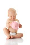 Bebé novo que joga com o banco piggy cor-de-rosa Imagem de Stock
