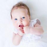 Bebé observado azul en un vestido blanco Imagen de archivo