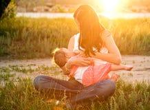 Bebé pecho-que introduce de la madre al aire libre. Puesta del sol del verano. Imagen de archivo