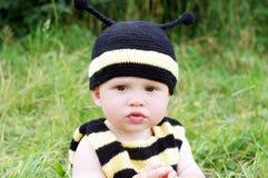 Bebé pensativo en traje de la abeja al aire libre Fotos de archivo