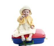 Bebé pequeno assentado em uns suitcas vermelhos e azuis Fotografia de Stock